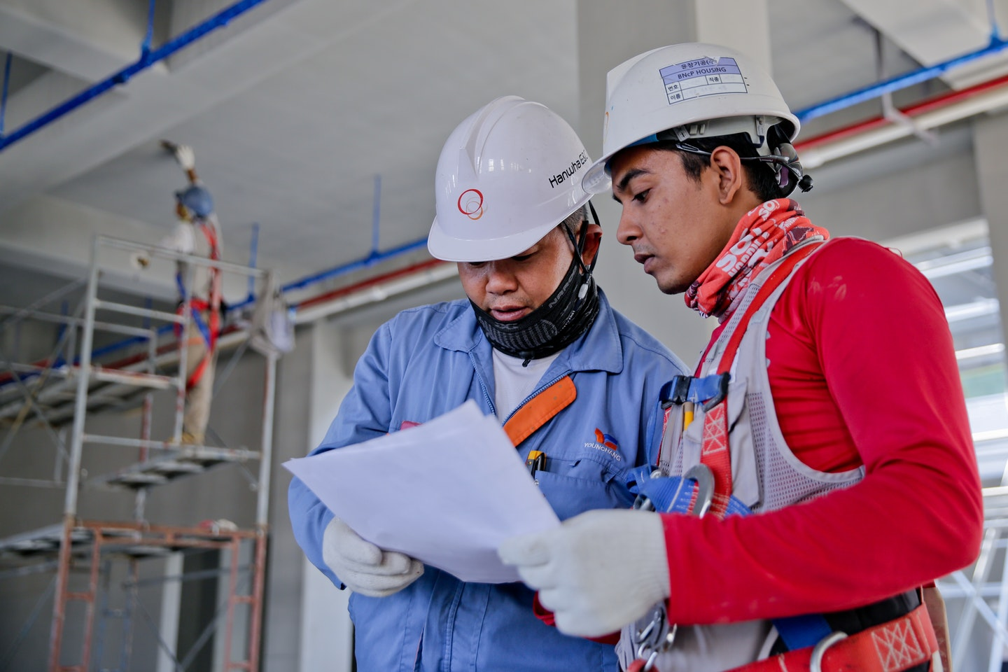 Two workers are reviewing a document while wearing safety gear